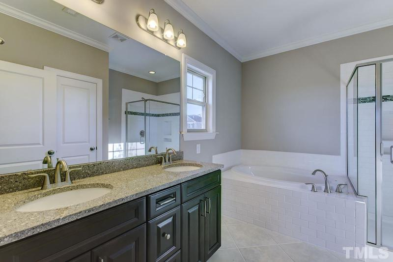 spacious master bathroom with twin vanities and large tub