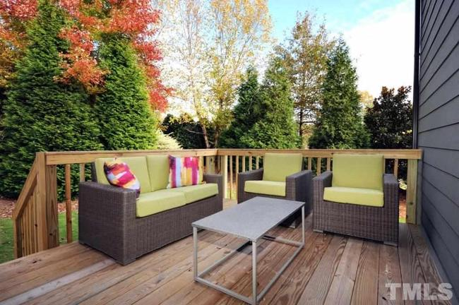 spacious back deck with landscaping