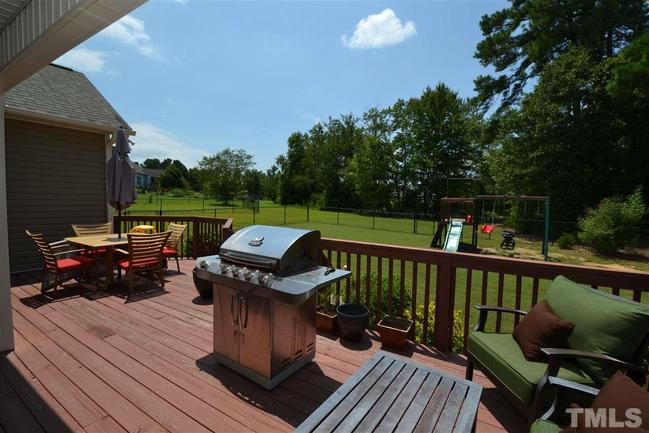 spacious deck overlooking backyard swingset