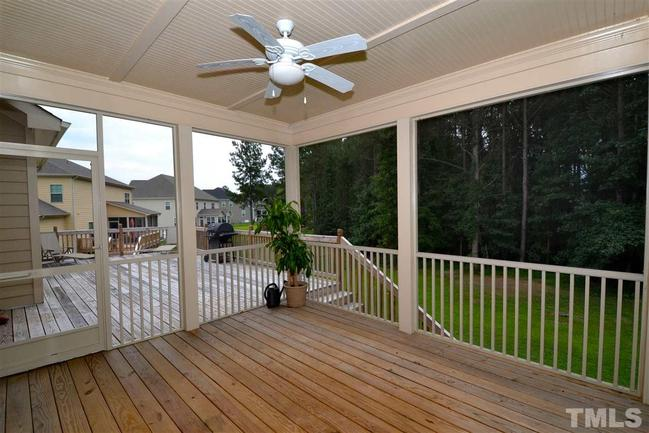 screened back porch and adjacent deck overlooking backyard