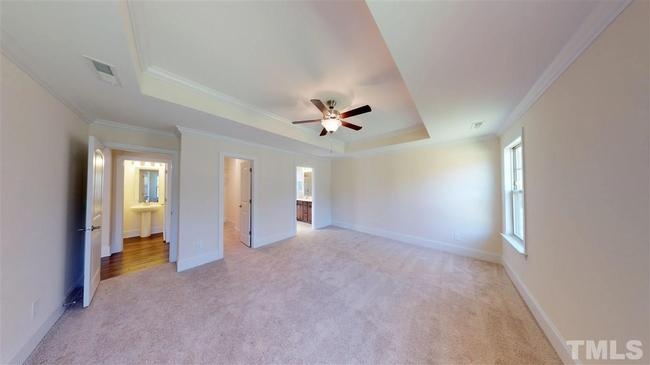 carpeted master suite with tray ceiling at 246 w wellesley drive